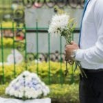 A man holding flowers at a funeral. Our Tennessee wrongful death lawyers can help you in your time of need.