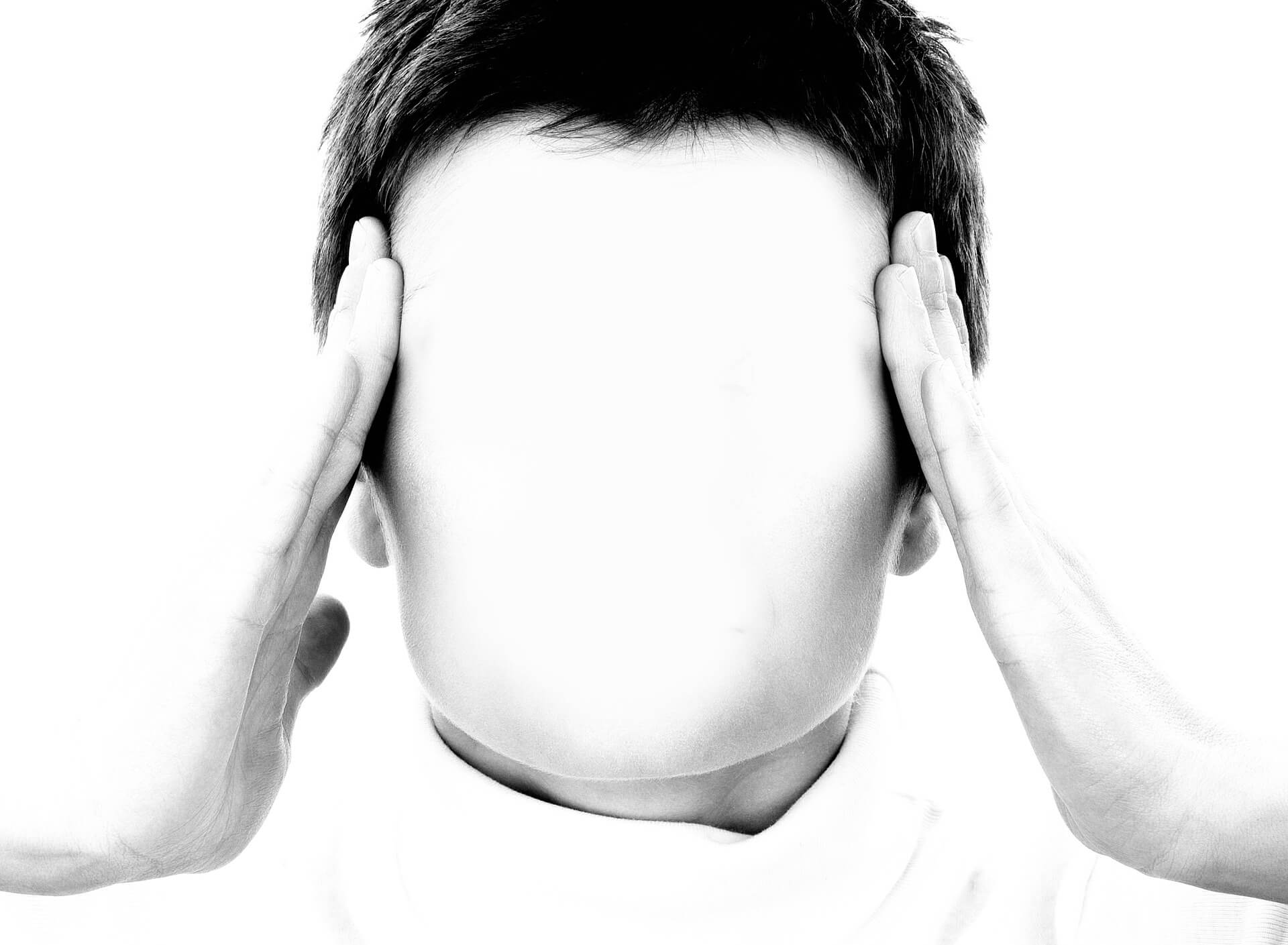 A man places his fingers at his temples as he is in pain. He is a candidate for a post-concussive syndrome lawsuit