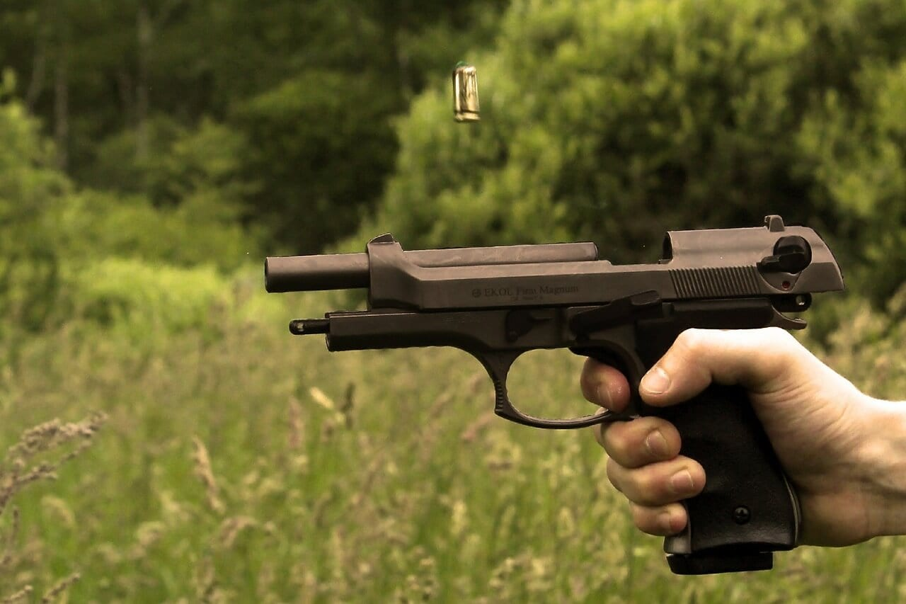 A handgun recoils as the trigger is pulled and a shell casing soars into the air