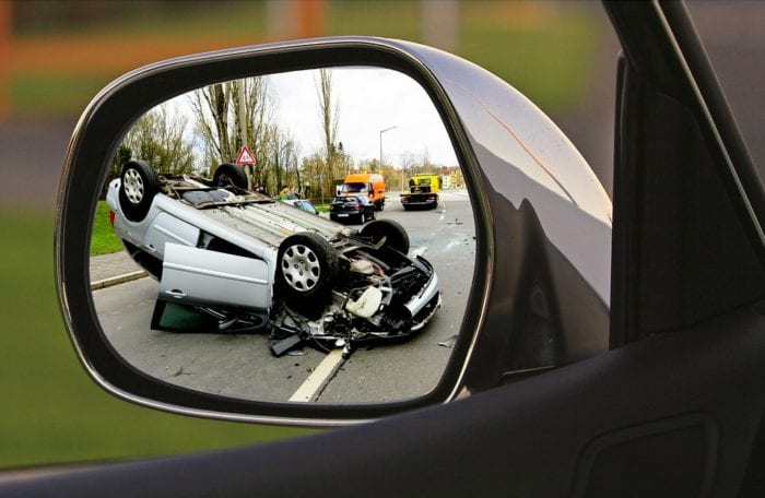 An overturned vehicle is pictured in a driver's side mirror. Call our Nashville car wreck lawyers today.