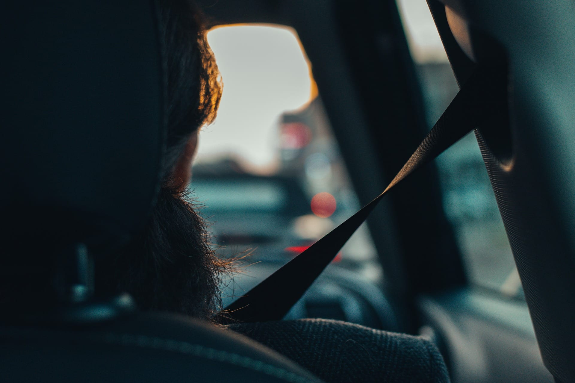 A woman is pictured with a shoulder seat belt in a motor vehicle